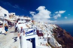 Grecia, Santorini - 1 de octubre de 2017: gente vacationing en las calles estrechas de las ciudades blancas en la isla Foto de archivo libre de regalías