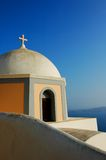Grecian Church. A pretty church built in typical Greek-style white stone. The round dome and golden cross stand out against the vibrant blue sky and surrounding Royalty Free Stock Images