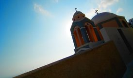 Grecian Church. A Grecian church with perfect white round domes is lit from the back by the blazing sun. This church in Santorini has grey and orange walls Royalty Free Stock Photos
