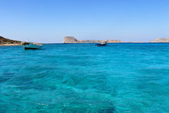 Grecja W lecie, dwa łodzi blisko wyspy w błękitnej lagunie Zdjęcie Stock