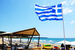 Grecka flaga na plaży cieszy się ich wakacje turystach i Fotografia Royalty Free