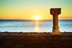 Grecka kolumna na brzeg i zmierzch nad morzem ukazujemy się zdjęcie royalty free