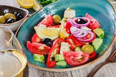 Grecka sałatka organicznie warzywa z pomidorami, ogórkami, czerwoną cebulą, oliwkami, feta serem i szkłem wino, obrazy royalty free