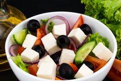 Grecka sałatka z świeżymi warzywami, feta serem i czarnymi oliwkami na ciemnym tle, zdjęcie royalty free