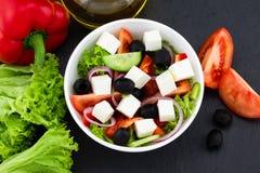 Grecka sałatka z świeżymi warzywami, feta serem i czarnymi oliwkami na ciemnym tle, Odgórny widok fotografia royalty free