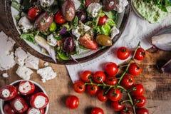 Grecka sałatka z czereśniowymi pomidorami, cebulami, antipasti i feta serem na drewnianym stołowym odgórnym widoku, obrazy royalty free
