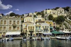 Grecka wyspa z pastelowymi barwionymi domami pod jasnymi niebieskimi niebami Fotografia Royalty Free