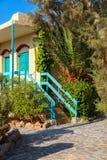 Grecki koloru żółtego dom z błękitnymi drewnianymi roślinami na dla i elementami zdjęcia royalty free
