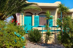 Grecki koloru żółtego dom z błękitnymi drewnianymi roślinami na dla i elementami obrazy stock