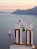 Greckokatolickiego kościół Dzwonkowy wierza przeciw morzu egejskiemu z żeglowanie łodzią przy zmierzchem, Santorini Zdjęcie Royalty Free