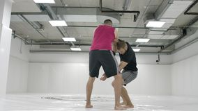 Greco-Roman wrestlers in a white room with mats. Practicing self-defense techniques. Throw and pain.  stock footage