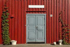 Gred door with red wooden wall Stock Photo