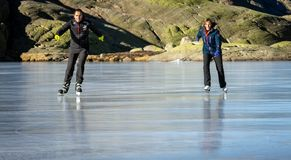 Gredos, Spain. 12-January-2019. Horizontal picture of couple ice skating outdoors on a frozen lake during a lovely sunny winter stock photography