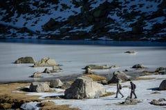Gredos Spanien 12-January-2019 Två trekkers som går på snön in mot en djupfryst sjö under en härlig solig vinterdag royaltyfria bilder