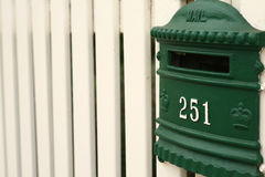 Greean mailbox on white picket fence Royalty Free Stock Photography