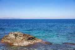 Greece. Aegean sea. Blue sky and calm sea water texture background. Greece. Aegean sea, Blue clear sky and calm sea. A big rock in the sea stock images