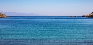 Greece. Aegean sea. Blue sky and calm sea water texture background. Greece. Aegean sea. Blue sky, calm turquoise sea water and snowed mountains royalty free stock images
