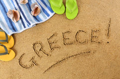 Greece beach. Writing : Greek beach background with towel and flip flops Royalty Free Stock Photos