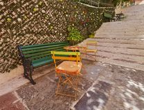 Greece, bench and chairs on pedestrian street Royalty Free Stock Photography