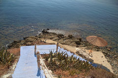 Greece, blue stairs to tranquil beach with umbrellas and chairs Royalty Free Stock Image