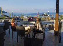 Greece, corfu, Agios Georgios, september 26, 2018: Two woman, mother and daugter having breakfast at outdoor hotel terrace restaur stock photo
