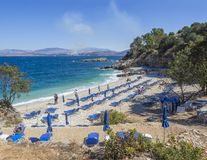 Greece, corfu, Kassiopi september 28, 2018: View of Bataria white sand beach with blue sunbeds and tourist people at royalty free stock photos