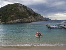 Greece, Corfu, Paleokastritsa, september 26, 2018: red motorboat and tourist boats parking at pier at Paleokastritsa bay stock photos