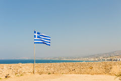 Greece Crete Island old Citadel Fort Fortezza fortress wall develops Greek flag on the background of the Mediterranean Sea Stock Photo