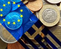 Greece crisis. European flag and flag of Greece over a bunch of Greek euro coins Stock Image