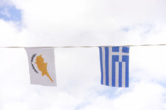Greece and Cyprus flags against blue cloudy sky royalty free stock image