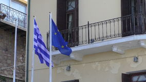 Greece and EU flags by the building. Greek and EU European Union flags waving together in a wind on poles by the balcony of the building facade with peeling off stock video footage