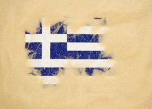 Greece flag. Damaged Greece flag buried under sand Stock Images