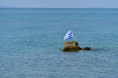 Greece flag in Aegean sea. View of Greece flag on a rock in the Aegean sea - rescue concept Stock Images