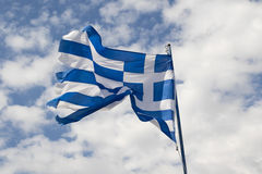 Greece flag against blue sky with white clouds. Greek flag flutter on wind against blue sky with white clouds Royalty Free Stock Photos