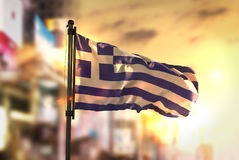 Greece Flag Against City Blurred Background At Sunrise Backlight. Sky Royalty Free Stock Photos