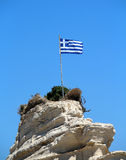 Greece flag on the cliff at the sea. Photo of Greece flag on the cliff at the sea royalty free stock image