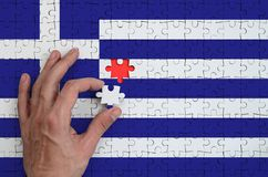 Greece flag is depicted on a puzzle, which the man`s hand completes to fold.  royalty free illustration