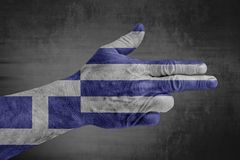 Greece flag painted on male hand like a gun. On concrete background royalty free stock image