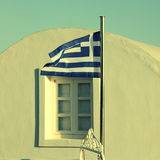Greece flag on sunset light in Oia, Santorini island. Stock Photos