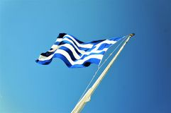 Greece flag waving on a blue sky stock images