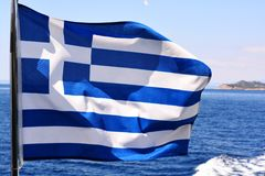 Greece national flag waving in wing on a boat, against blue sky and turquoise water. Greece flag waving in wing on a boat, against blue sky and turquoise water Stock Photo