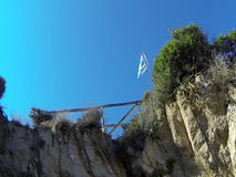 Greece fluttering flag on the top of a cliff stock footage