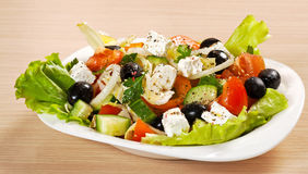 Greece fresh salad. Greece vegetable salad on a white plate Stock Photos