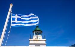 Greece. Kea island lighthouse. Greek flag waving on blue sky background. Greece. Kea island lighthouse. Greek flag waving on  clear blue sky background stock images