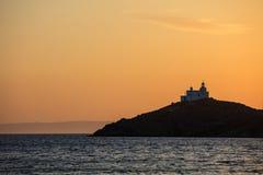 Greece, Kea island. Lighthouse at sunset. Greece, Kea island. Lighthouse on a cape at sunset stock photos