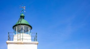Greece. Kea island lighthouse. Lighthouse tower and weather vane on blue sky background. Greece. Kea island lighthouse. Lighthouse tower and weather vane detail royalty free stock photos