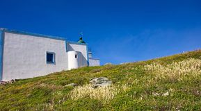 Greece. Kea island lighthouse. White color building on blue sky background. Greece. Kea island lighthouse. White color building, colorful wild flowers on green stock photos