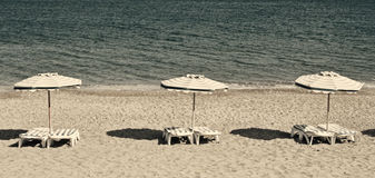 Greece. Kos island. Chairs and umbrellas on the Kefalos beach. I Royalty Free Stock Images