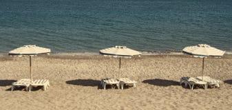 Greece. Kos island. Chairs and umbrellas on the Kefalos beach. I Royalty Free Stock Photos