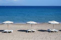 Greece. Kos. Kefalos beach. Chairs and umbrellas on the beach Royalty Free Stock Photography